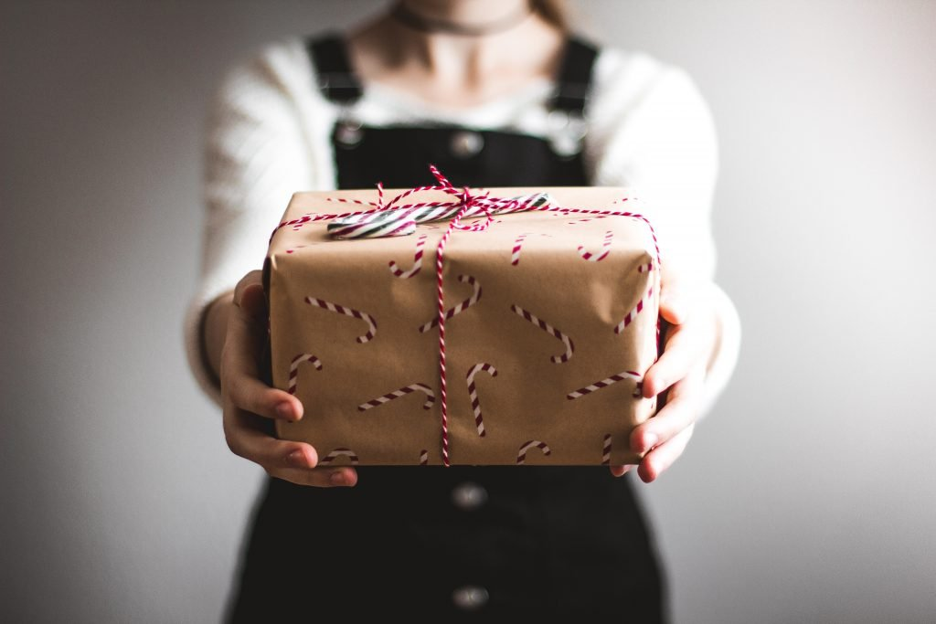 a woman holding a present wrapped in sustainable wrapping